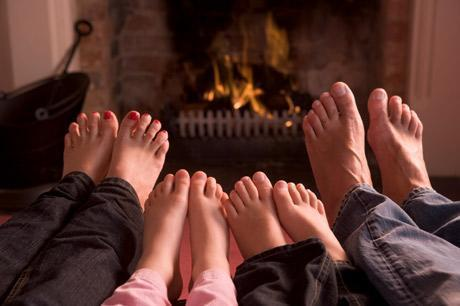 four family feet by fireplace